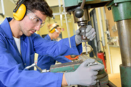 trainees: serious trainees focused on drilling metal piece with professional machinery