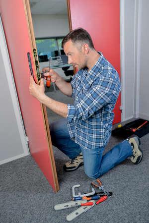 hinged: man fixing a door