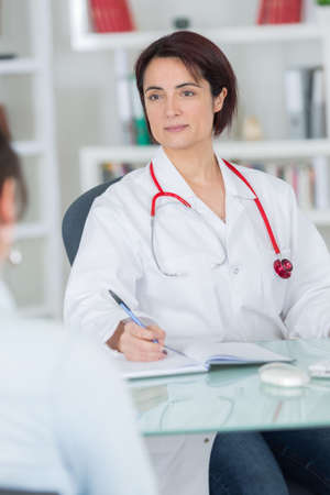 sick woman complaining to doctor about symptoms of malaise
