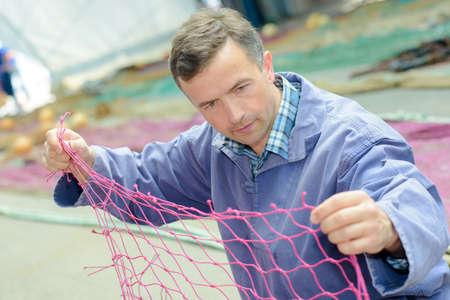 untangle: fisherman untangling net
