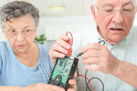 withdrawn: Elderly couple testing computer hard drive with multimeter