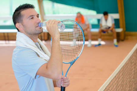 Man drinking from water bottle on tennis court Stock Photo