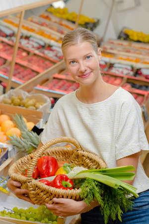 Señora que sostiene la cesta de frutas y verduras Foto de archivo