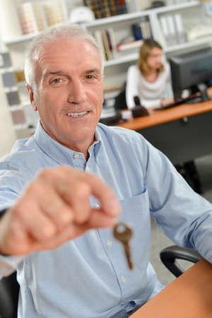 letting: Man holding forward a key