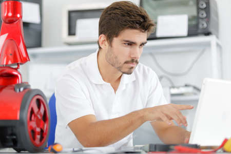 handsome engineer researching manufacturing issues with vacuum cleaner