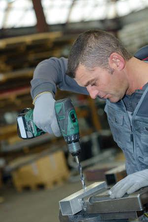 pierce: Man using cordless drill to pierce metal Stock Photo