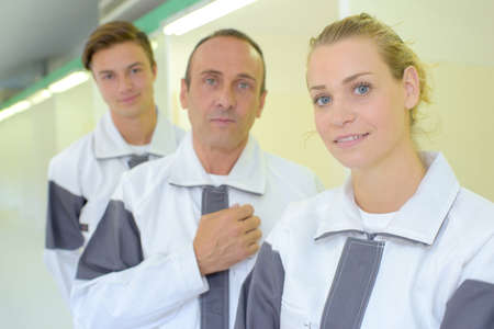 matching: Three workers in matching overalls Stock Photo