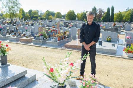 Man stood looking at gravestone Stock Photo