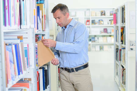 chinos: Man taking book from shelf in library