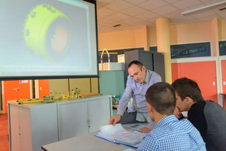 coursework: Teacher with students in front of screen
