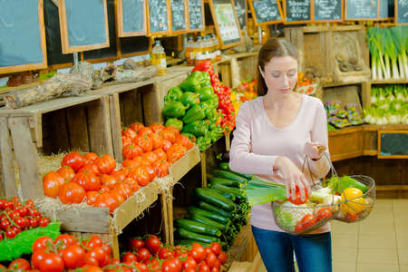 farm shop: Lady in farm shop holding basket of produce Stock Photo