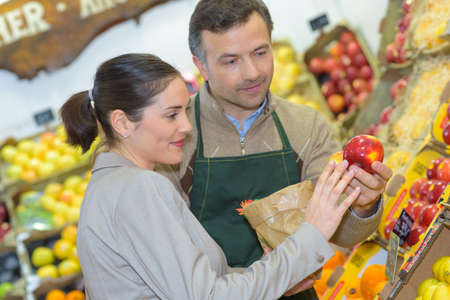 smiling woman choosing different fruits at farm food store display