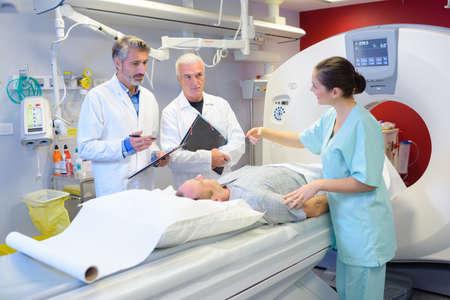 conversing: Medical staff stood around patient having scan