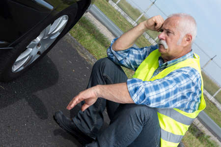 discouraged: discouraged retired man unable to change car tyre Stock Photo