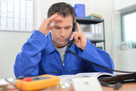 office tool: Electrician on the phone in his office Stock Photo