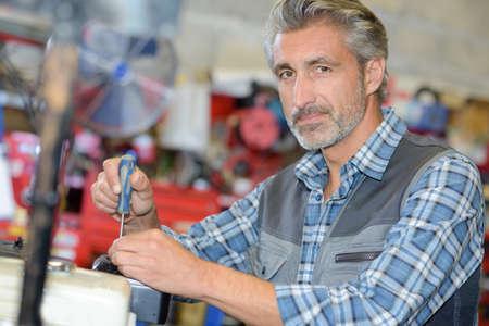tornillos: Portrait of mechanic using screwdriver