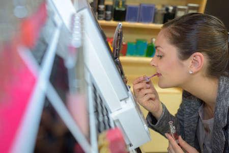 millennial: beautiful young woman buying lipstick