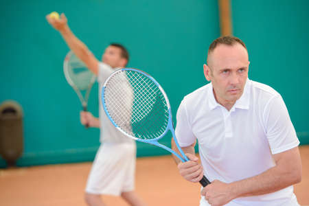 serf: Men playing doubles tennis Stock Photo