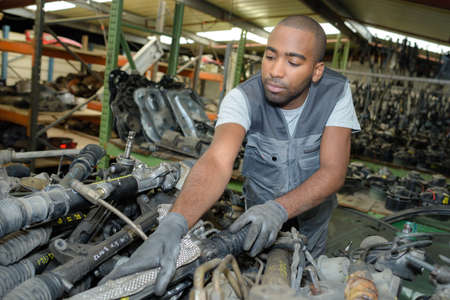 recycles: Mechanic at stack of used car parts