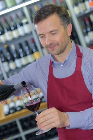 Wine merchant pouring glass of red