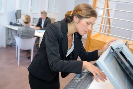 fotocopiadora: Mujer que usa la fotocopiadora Foto de archivo