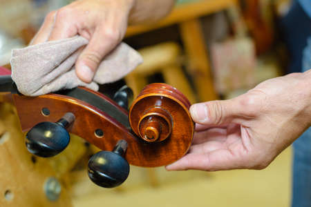 Hands polishing end of musical instrument
