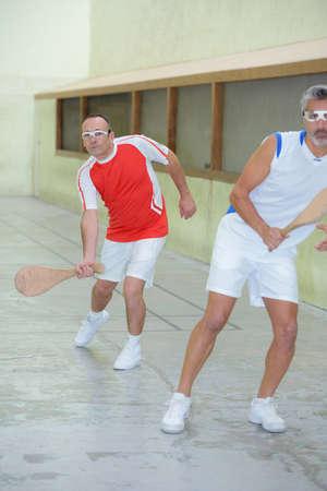 ballgame: Men playing squash with wooden racket