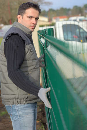 mesh: worker erecting a fence