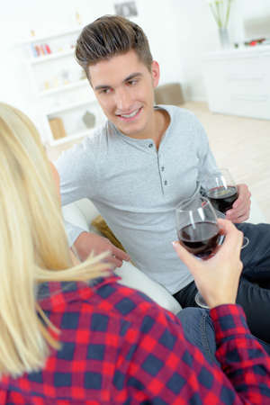 Couple on sofa holding wineglasses