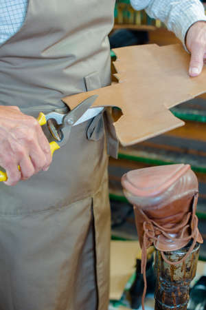 secateur: Cobbler cutting out new sole for boot