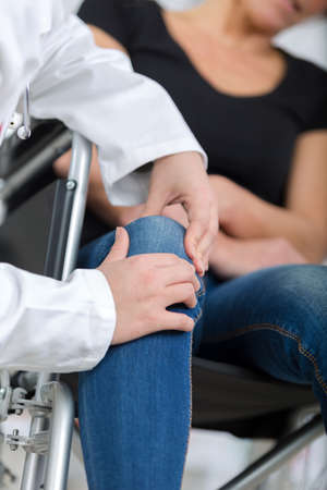 suffers: female handicapped suffers pain in her knee doctor ausculting