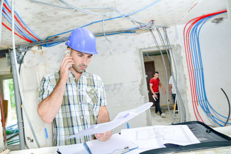 Worker phoning and examining sketches Stock Photo
