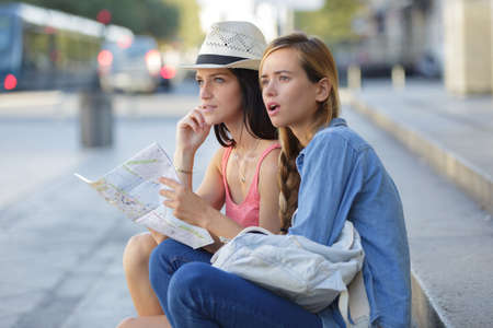navigator: lost and confused girl friends looking for directions on map