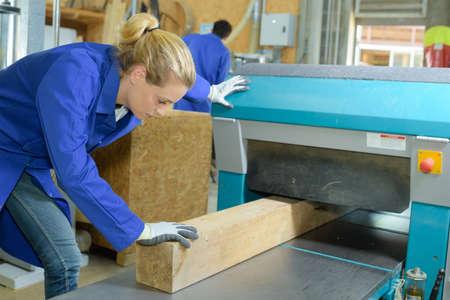 feeding through: Woman feeding wood through machine