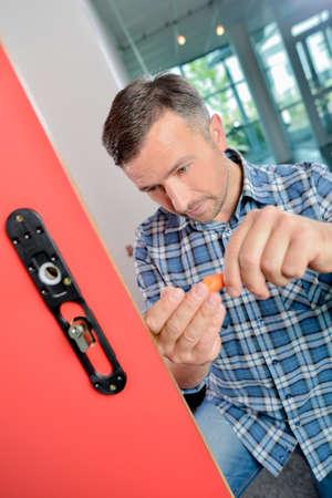 fire surround: Man fitting lock to internal door