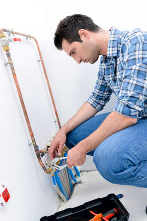 condensing: Plumber making adjustments to the heating system
