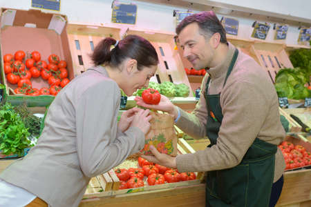 Grocer holding tomato for customer to smell