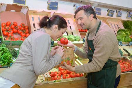Grocer tenant la tomate pour le client à l'odeur Banque d'images - 71484440