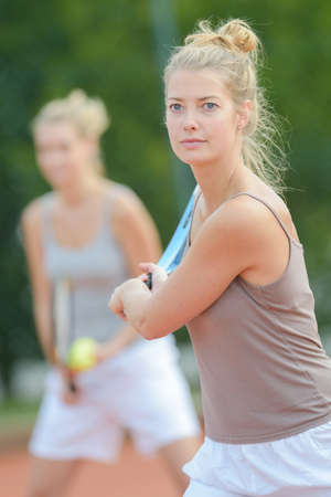 Women playing tennis doubles