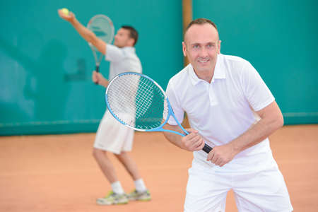 competitive sport: Men playng tennis doubles Stock Photo