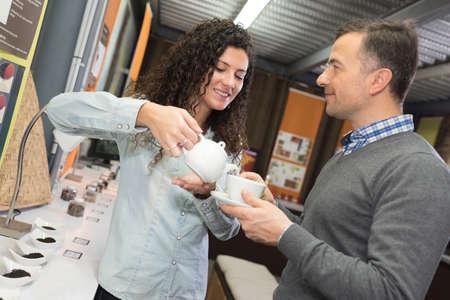 theine: woman pouring man tea in tea shop Stock Photo