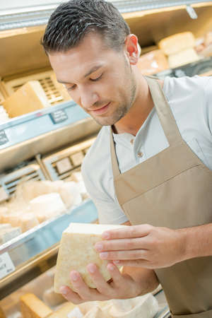 suggest: Shop worker holding expensive cheese