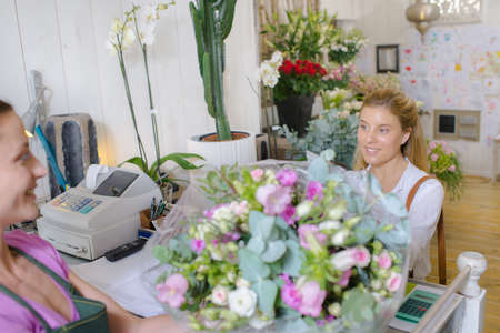 checkout: Worker and customer in florists, at checkout