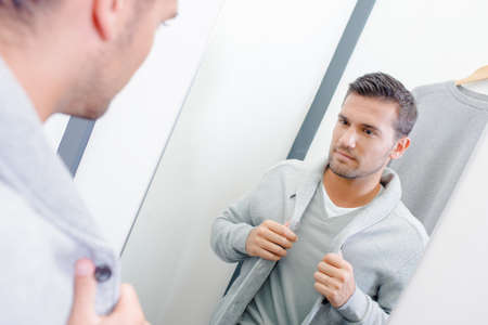 lapels: Man trying on jacket in fitting room