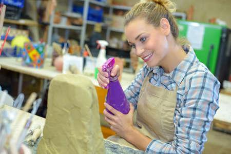 dampen: Female artist spraying water onto clay