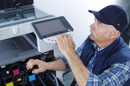 male technician repairing digital photocopier machine