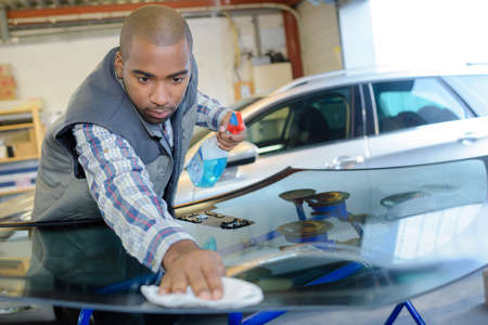 conscientious: Garage worker polishing replacement windscreen