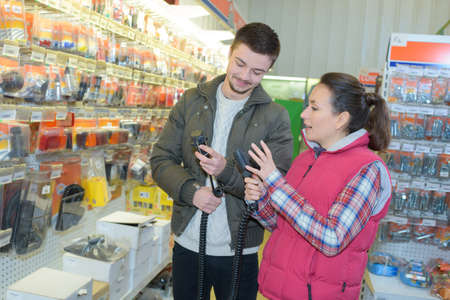 retailer: saleswoman assisting male customer at hardware store