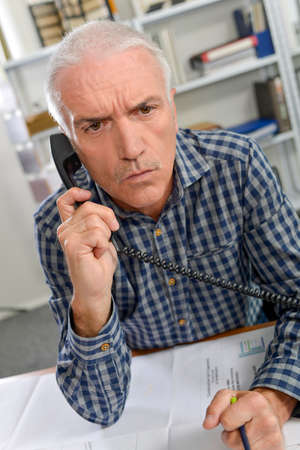 Man on telephone, frowning Stock Photo
