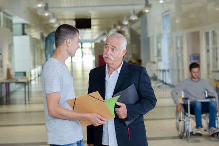 men talking: Two men talking in corridor